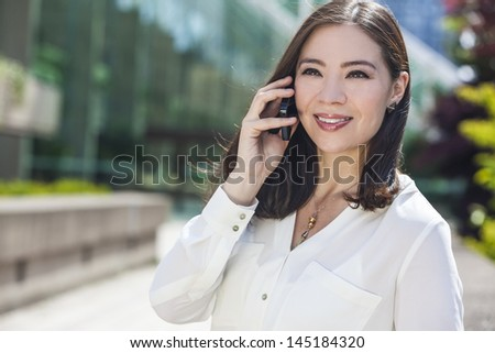 Portrait of a smiling happy young Asian woman or businesswoman talking on her cell phone