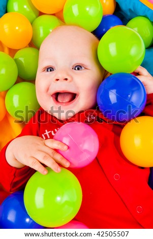 Portrait of a smiling infant lying with colorful balls