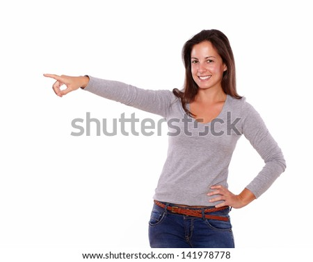 Portrait of a smiling lady pointing to her right looking at you on white background - copyspace