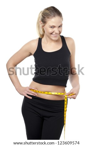 Portrait of a smiling lady with tape measure measuring her waist - stock photo