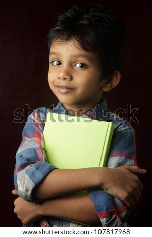 Portrait of a smiling little boy holding a book