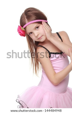 Portrait of a smiling little dancer in pink tutu standing in a ballet pose - stock photo