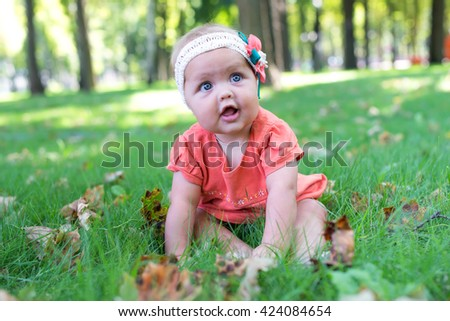 Portrait of a smiling little girl close up. Cute three years old child enjoying nature outdoors. Healthy carefree kid playing outside in summer park. - stock photo