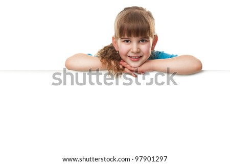 Portrait of a  smiling little girl   leaning on blank board  against white background. Lots of copyspace for your text and logo. Advertising concept. Isolated on white