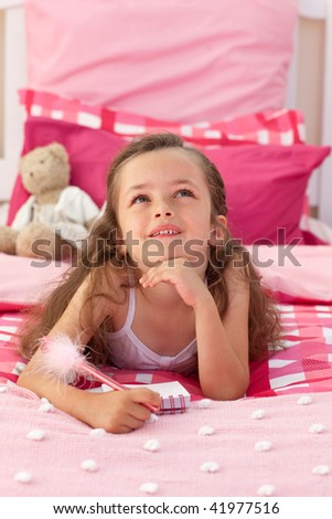 Portrait of a smiling little girl lying on bed - stock photo