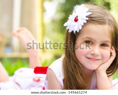 Portrait of a smiling little girl lying on green grass - stock photo