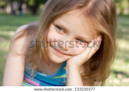 portrait of a smiling little girl outdoors