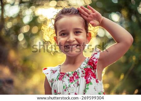 Portrait of a smiling little girl, sunset shot - stock photo