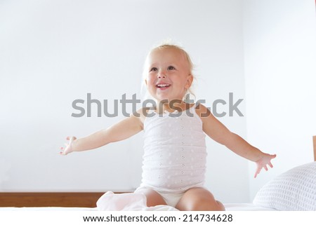 Portrait of a smiling little girl with arms outstretched in bed room - stock photo