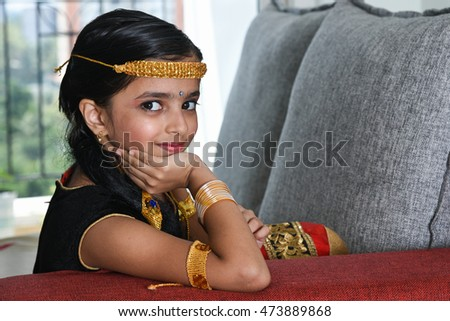 Portrait of a smiling little Indian girl/child/kid in dance pose/performing dance dressed up in its costume, North India. In inviting posture/in welcome posture. Beautiful Bollywood dancer