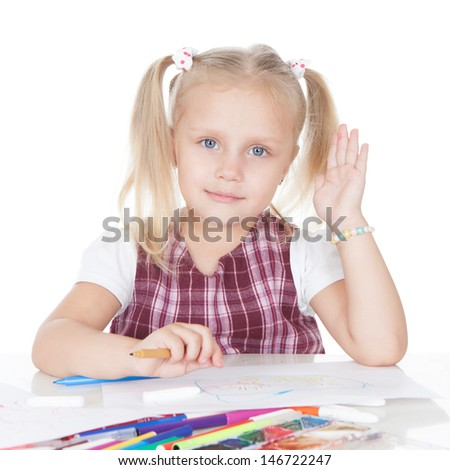 Portrait of a smiling little schoolgirl at the desk over white