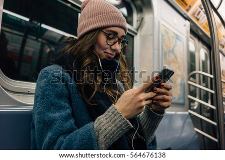 Portrait of a smiling lovely girl typing message on mobile phone in subway train