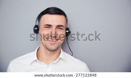 Portrait of a smiling male assistant in headphones looking at camera over gray background - stock photo