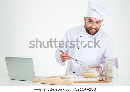 Portrait of a smiling male chef cook baking with laptop isolated on a white background - stock photo