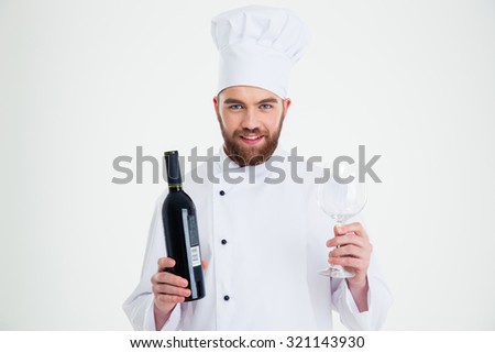 Portrait of a smiling male chef cook holding bottle of wine and wineglass isolated on a white background - stock photo