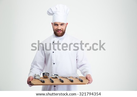 Portrait of a smiling male chef cook holding wooden chopping board with spoons isolated on a white background - stock photo