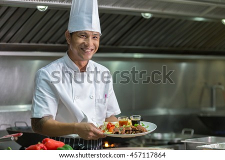 Portrait of a smiling male chef with cooked food standing in the kitchen, Chef Thailand - stock photo