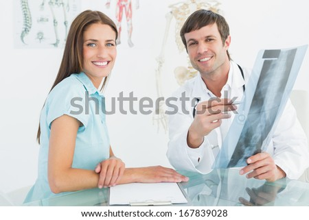 Portrait of a smiling male doctor explaining spine x-ray to female patient in the medical office
