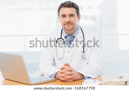 Portrait of a smiling male doctor with laptop sitting at desk in medical office - stock photo