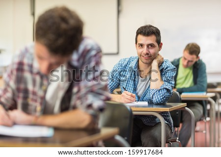 Portrait of a smiling male student with others writing notes in the classroom - stock photo