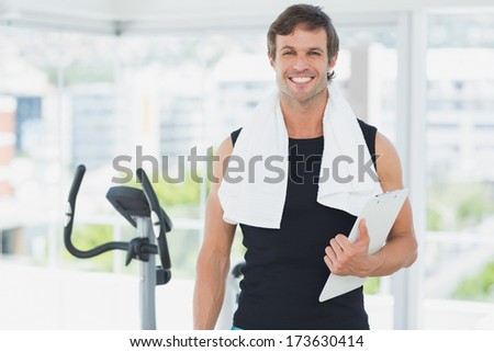 Portrait of a smiling male trainer with clipboard standing in a bright gym - stock photo