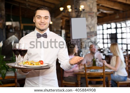 Portrait of a smiling male waiter with a tray in his hand at the restaurant
