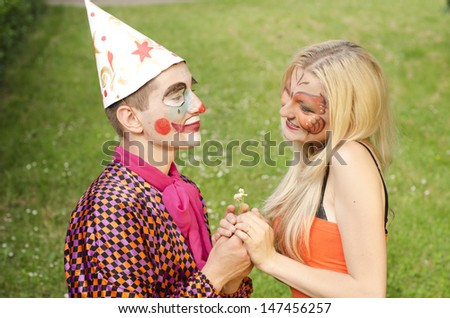 Portrait of a smiling man dressed like a clown trying to present a balloon to a happy girl with butterfly makeup