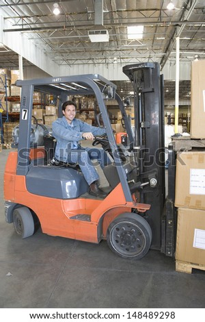 Portrait of a smiling man operating forklift truck in distribution warehouse - stock photo