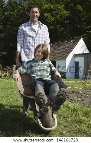 Portrait of a smiling man pushing son in wheelbarrow outside cottage