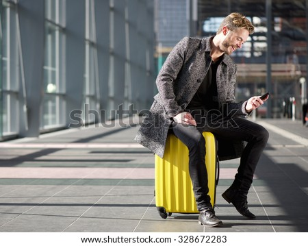 portrait of a smiling man resting at airport with mobile phone
