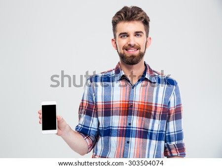 Portrait of a smiling man showing blank smartphone screen isolated on a white background. Looking at camera - stock photo