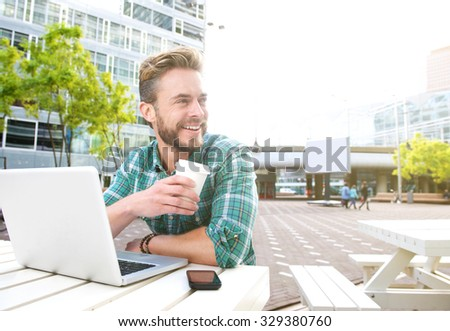 Portrait of a smiling man sitting outside with laptop and coffee  - stock photo