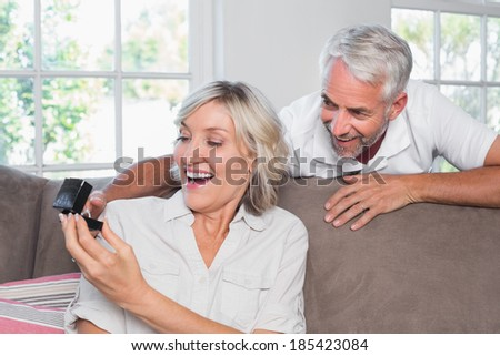 Portrait of a smiling man surprising woman with a wedding ring at home - stock photo