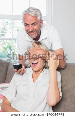 Portrait of a smiling man surprising woman with a wedding ring at home