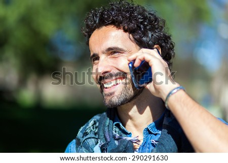 Portrait of a smiling man talking on the phone - stock photo