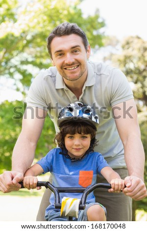 Portrait of a smiling man teaching his son to ride a bicycle - stock photo