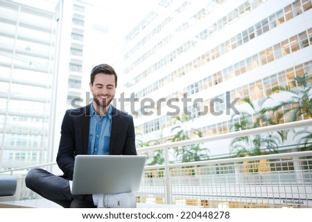 Portrait of a smiling man using laptop computer indoors - stock photo