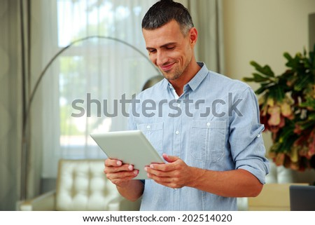Portrait of a smiling man using tablet computer at home - stock photo