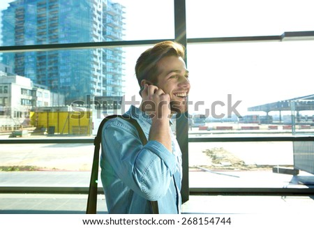 Portrait of a smiling man walking and talking on mobile phone at the airport - stock photo
