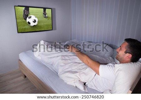 Portrait Of A Smiling Man Watching Football Match On Television In Bedroom - stock photo