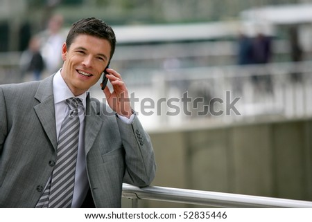 Portrait of a smiling man with a phone - stock photo