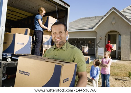 Portrait of a smiling man with box while family unloading delivery van in the background by new house - stock photo