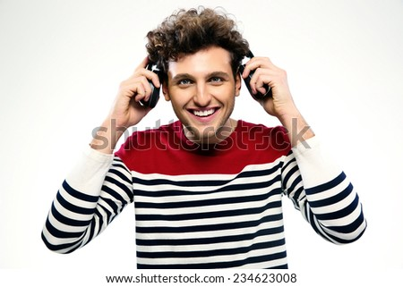 Portrait of a smiling man with headphones over gray background - stock photo