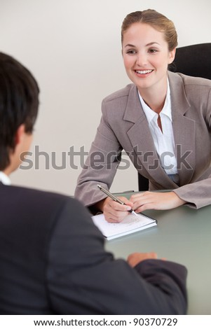 Portrait of a smiling manager interviewing a male applicant in her office - stock photo