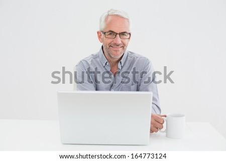 Portrait of a smiling mature businessman with laptop and coffee cup against white background