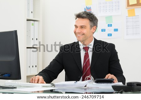 Portrait Of A Smiling Mature Businessman Working At Office Desk - stock photo