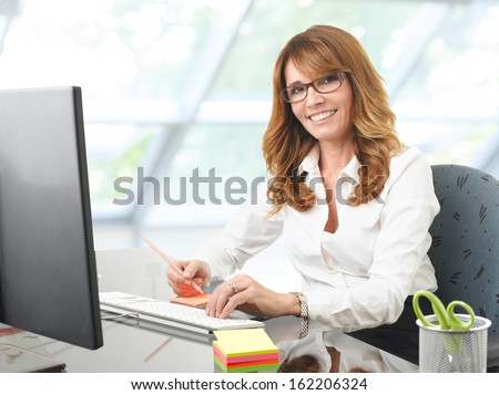 Portrait of a smiling mature businesswoman at office desk with a computer - stock photo