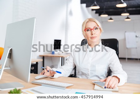 Portrait of a smiling mature businesswoman working in office - stock photo