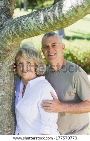 Portrait of a smiling mature couple besides a tree at the park