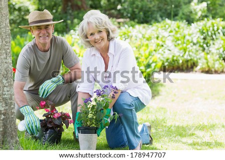 Portrait of a smiling mature couple engaged in gardening